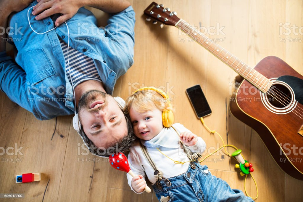 Father and son with smartphone and earphones, listening music. stock photo