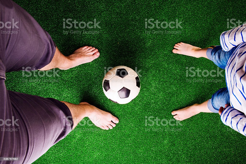 Father and son with soccer ball against green grass stock photo