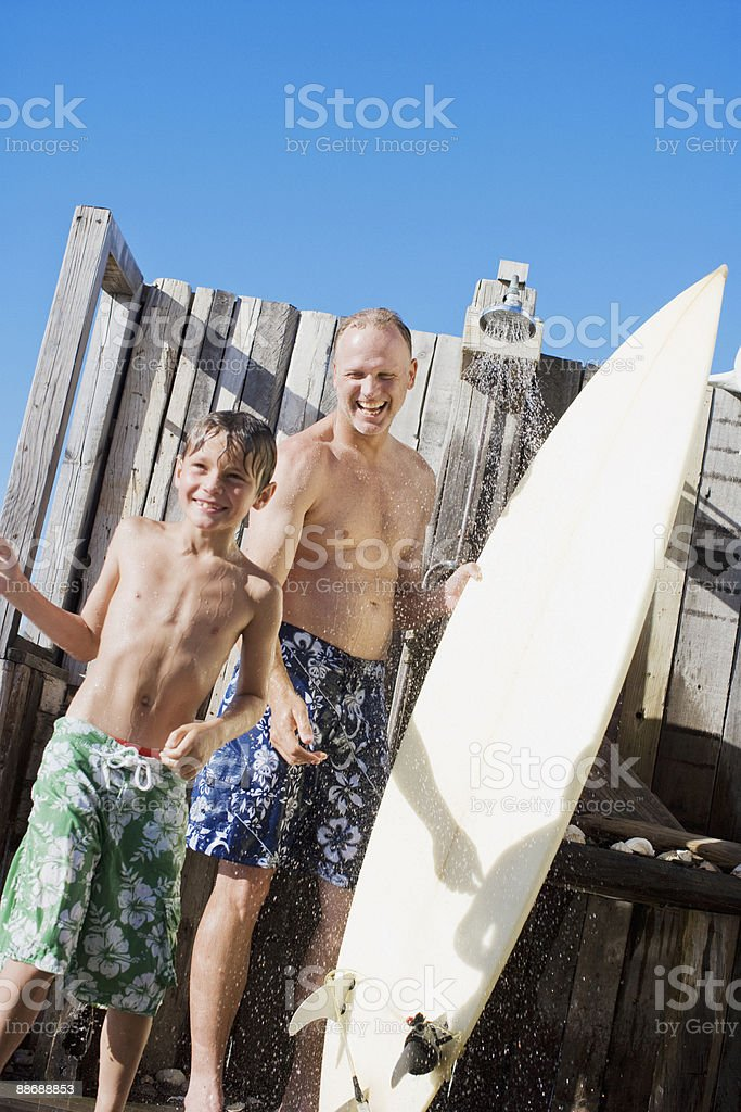 Father and son with surfboard rinsing off outdoors royalty-free stock photo