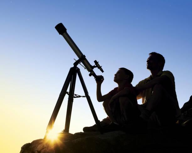 père et fils avec télescope - astronomie photos et images de collection