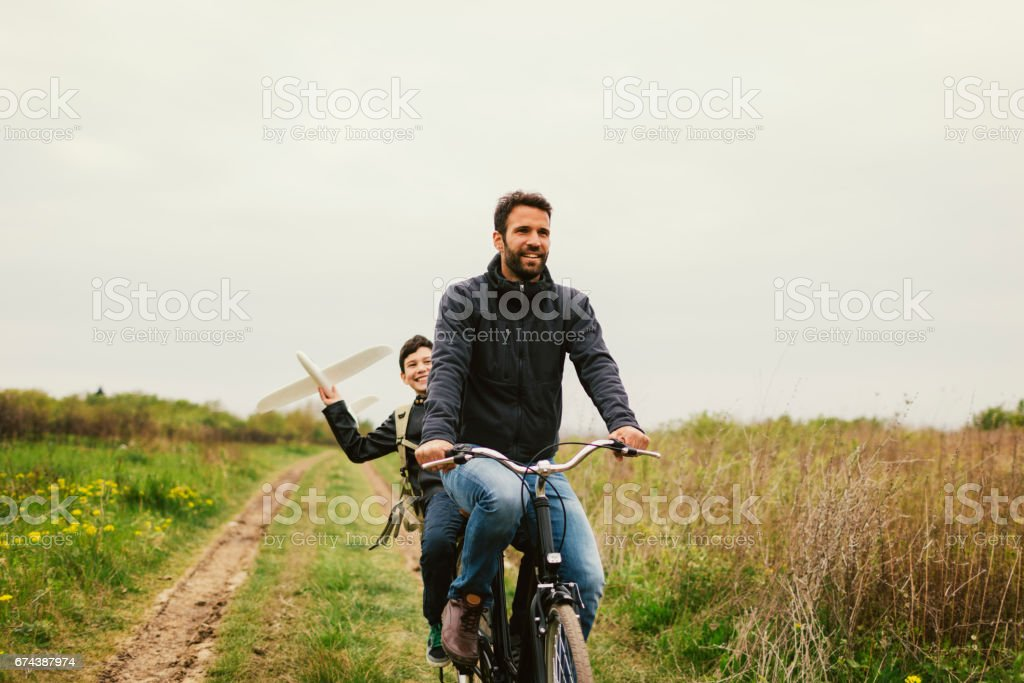 Father and son with toy plane outdoors stock photo