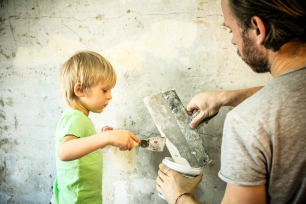 Father and son with trowel plastering a wall stock photo