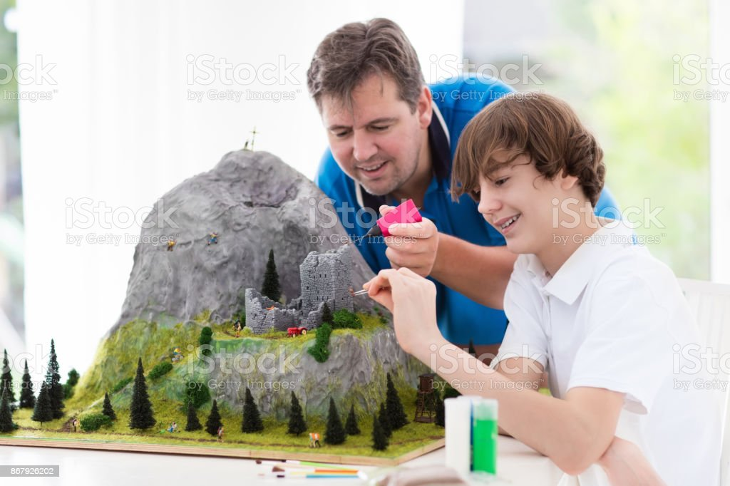 Father and son work on model building project stock photo