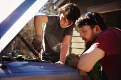 Father teaching son to work on a truck