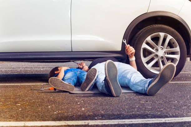 Vater und Sohn gemeinsam unter kaputtes Auto – Foto