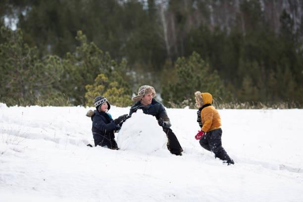vater und söhne spielen im schnee - schneemann bauen stock-fotos und bilder