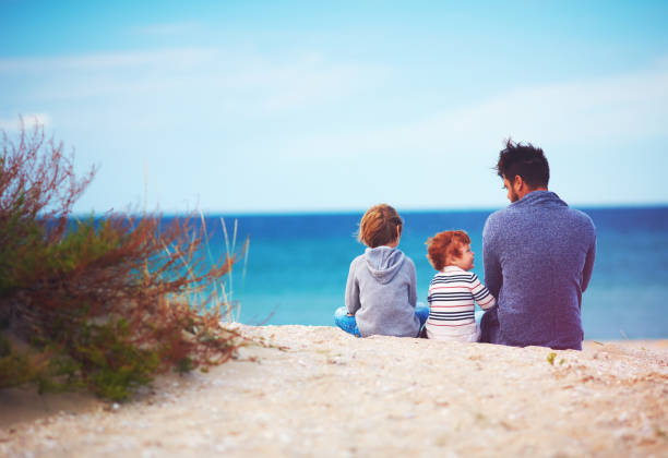 father and sons at sandy beach near the sea on windy day stock photo