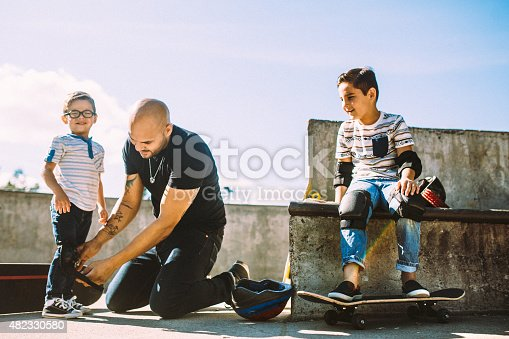 A fun, playful Hispanic Dad and his two boys play together at a skate park. The father helps his sons put on helmets and padding so they can skateboard safely.   Horizontal with copy space.