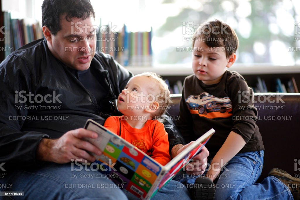Father and sons at the library stock photo