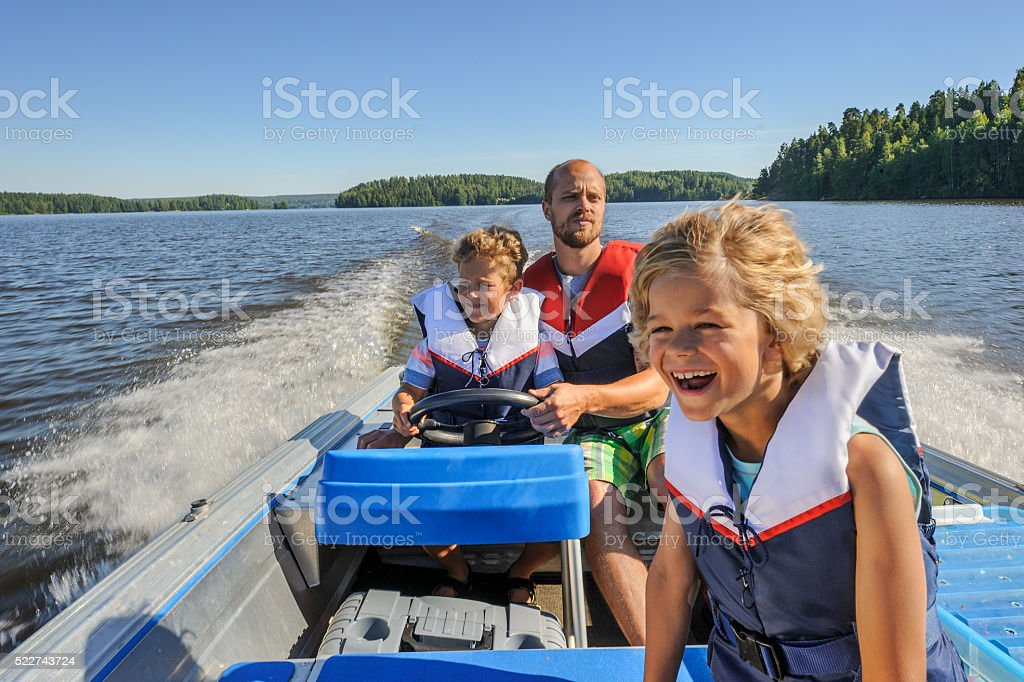 father and sons boating stock photo