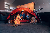 A dad with his two sons camp inside their home due to the coronavirus restrictions and quarantine. They have pitched a tent along with stuffed animal friends and have a fake campfire next to a telescope. They are making the best of their situation and long to return to the outdoors.