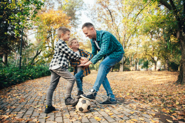 Father and sons having fun playing with ball stock photo stock photo