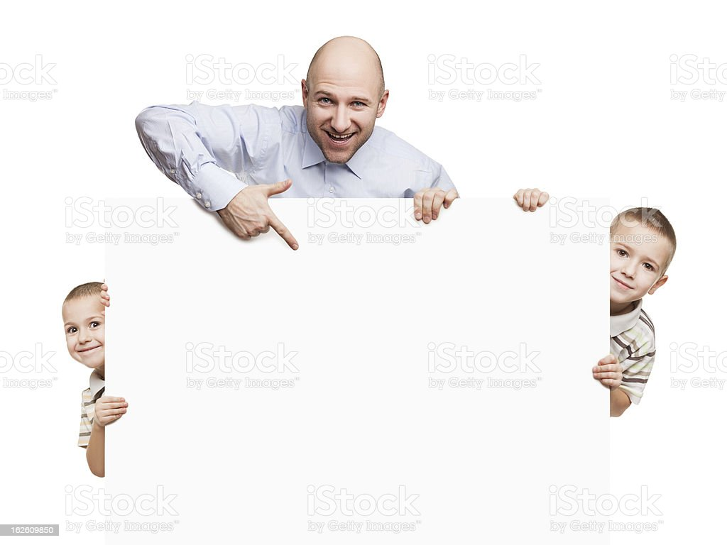 Father and sons holding blank sign or placard royalty-free stock photo