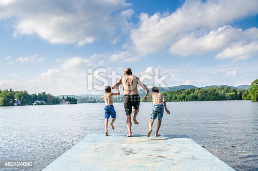 509813720 istock photo Father and sons jumping in lake 482424050