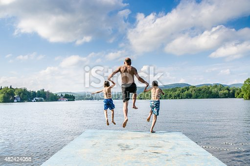 509813720 istock photo Father and sons jumping in lake 482424058