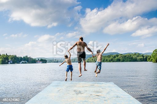 509813720 istock photo Father and sons jumping in lake 482424062