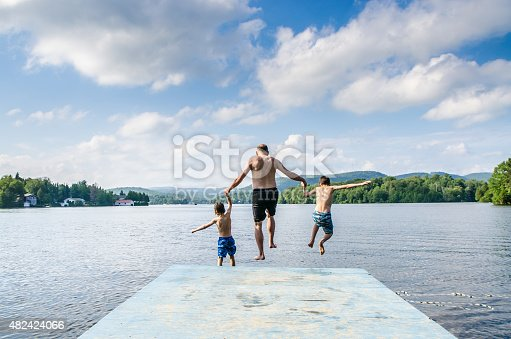 509813720 istock photo Father and sons jumping in lake 482424066