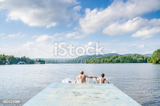 509813720 istock photo Father and sons jumping in lake 482424068