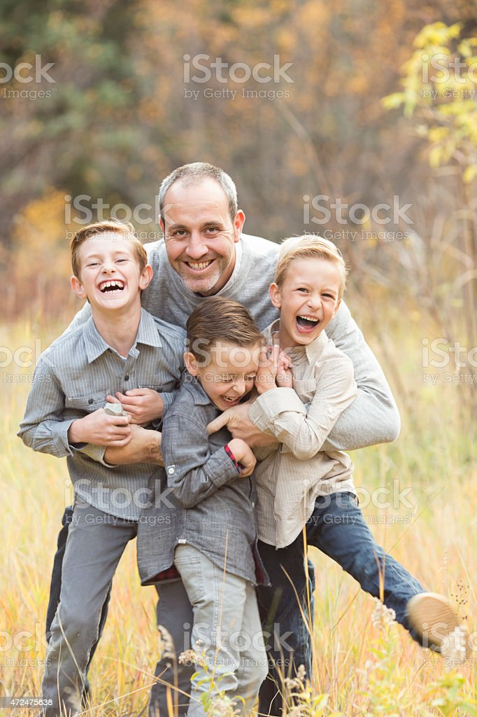 Father and sons laughing and playing stock photo