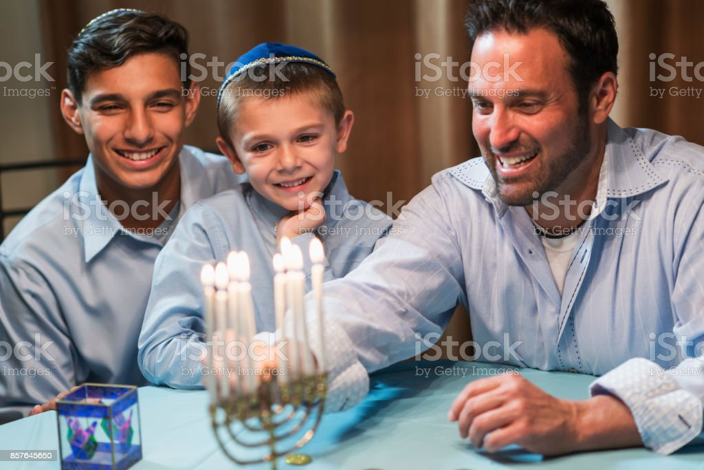Father and sons lighting menorah stock photo