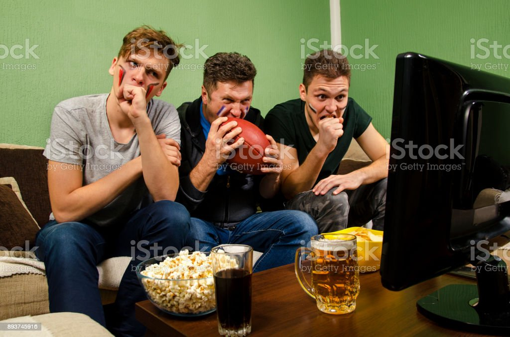 Father and sons nervously watching american football stock photo