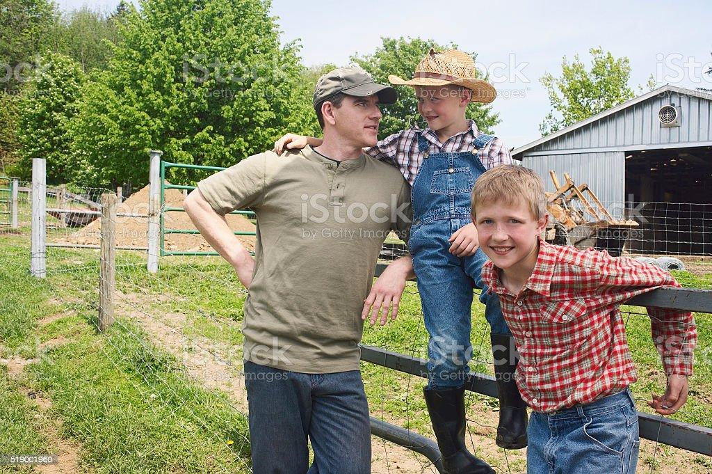 Father and sons on farm stock photo