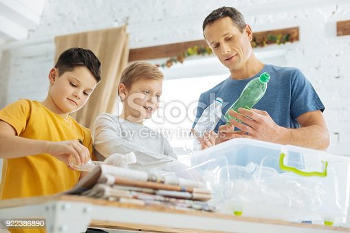 istock Father and sons preparing plastic bottles for recycling 922386890
