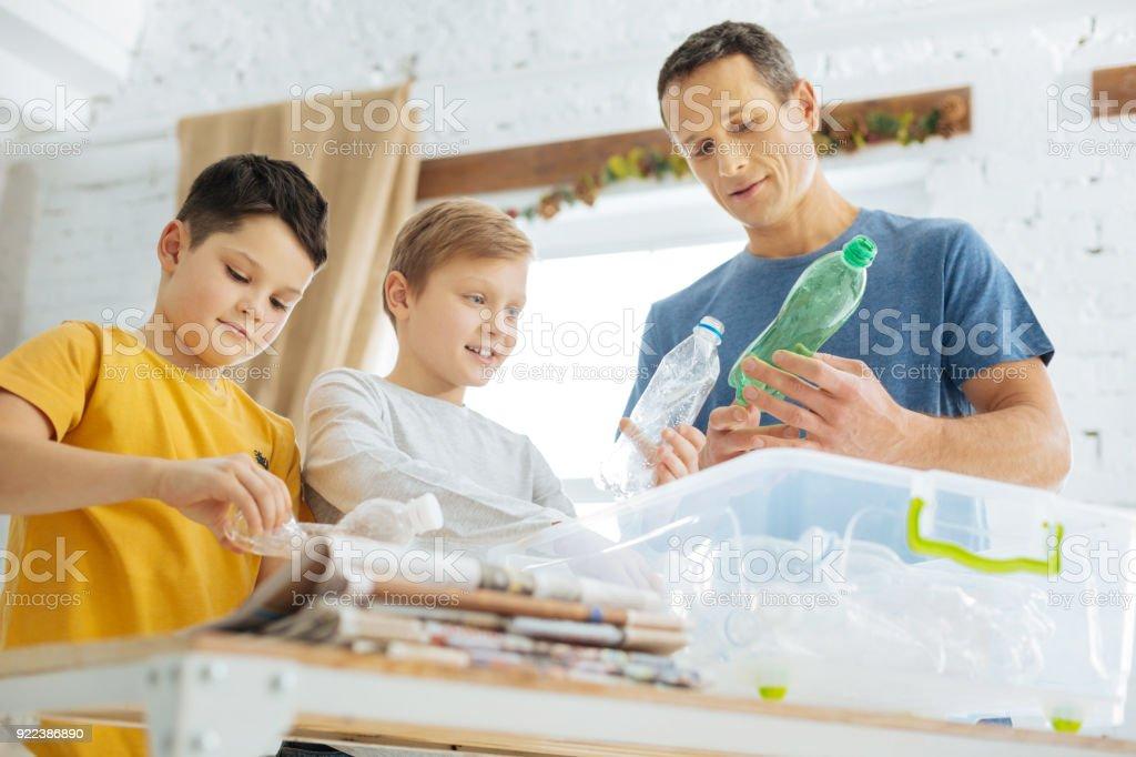 Vater und Söhne, die Vorbereitung von Kunststoff-Flaschen für das recycling – Foto