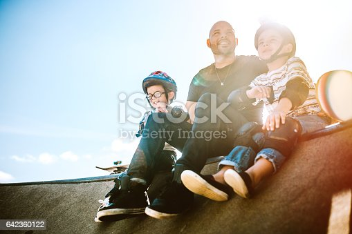A fun, playful Hispanic Dad and his two boys play together at a skate park. They boys have helmets and padding, and are ready to have fun with their father. The young family of three takes a minute to rest together. A sun flare shines behind them. Horizontal with copy space.