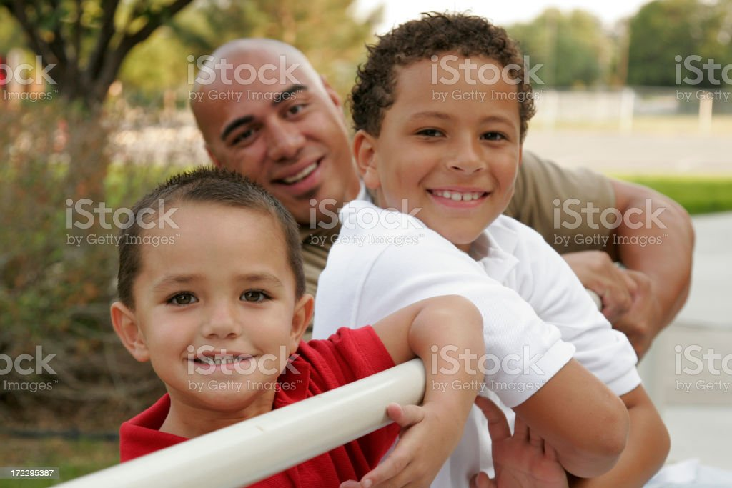 Father and sons smiling and leaning against white railings stock photo