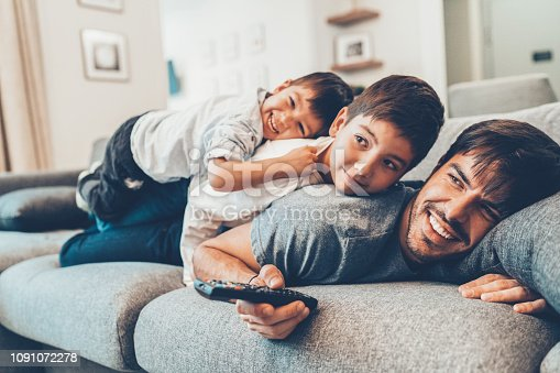 Young beautiful father and two sons watching tv
