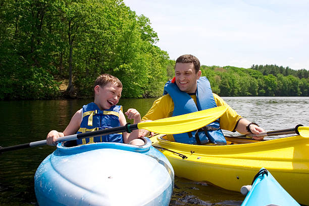 Father and sun smiling and kayaking stock photo