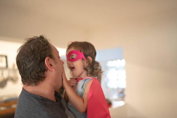 far och superhjälte dotter omfamna hemma - superwoman barn bildbanksfoton och bilder