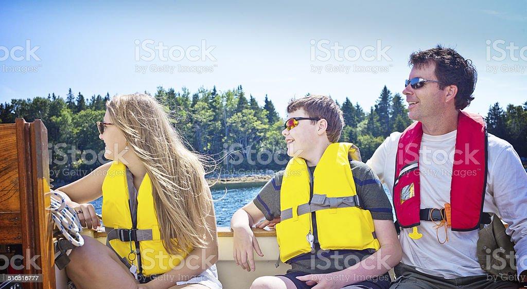 Father and Teenage Children Sailing on Mahone Bay, Nova Scotia stock photo