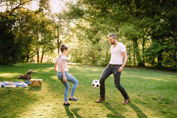 father and teenage daughter playing soccer in park - kinder picknick spiele stock-fotos und bilder