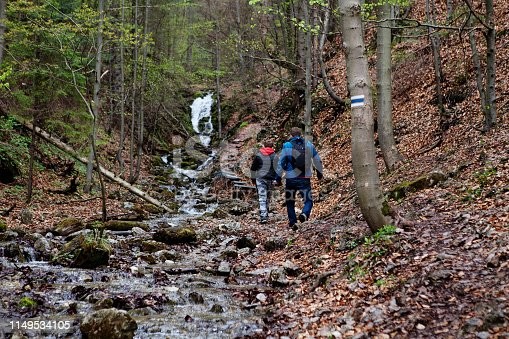 Tatranska Lomnica, Slovakia - April 29, 2019: back view of a parent with a kid walking up the wet gorge hiking trail on a rainy overcast cold day