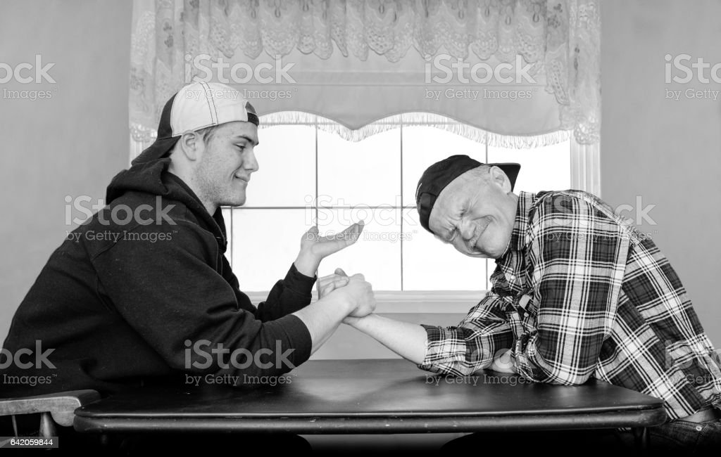 father and teenage son armwrestling. stock photo