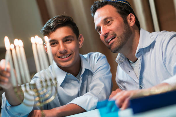 Father and teenage son lighting menorah stock photo
