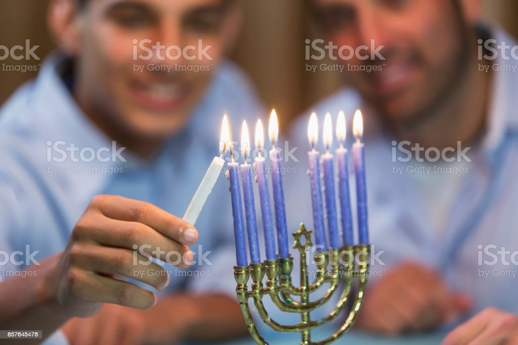 Father and teenage son lighting menorah stock photo
