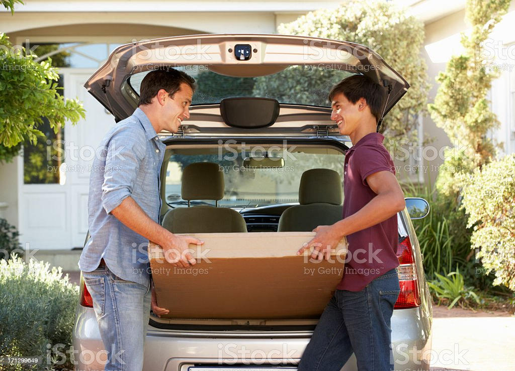 Father And Teenage Son Loading Package Into Back Of Car stock photo
