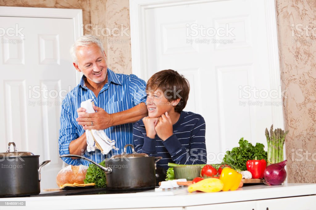Father and teenage son talking in kitchen royalty-free stock photo