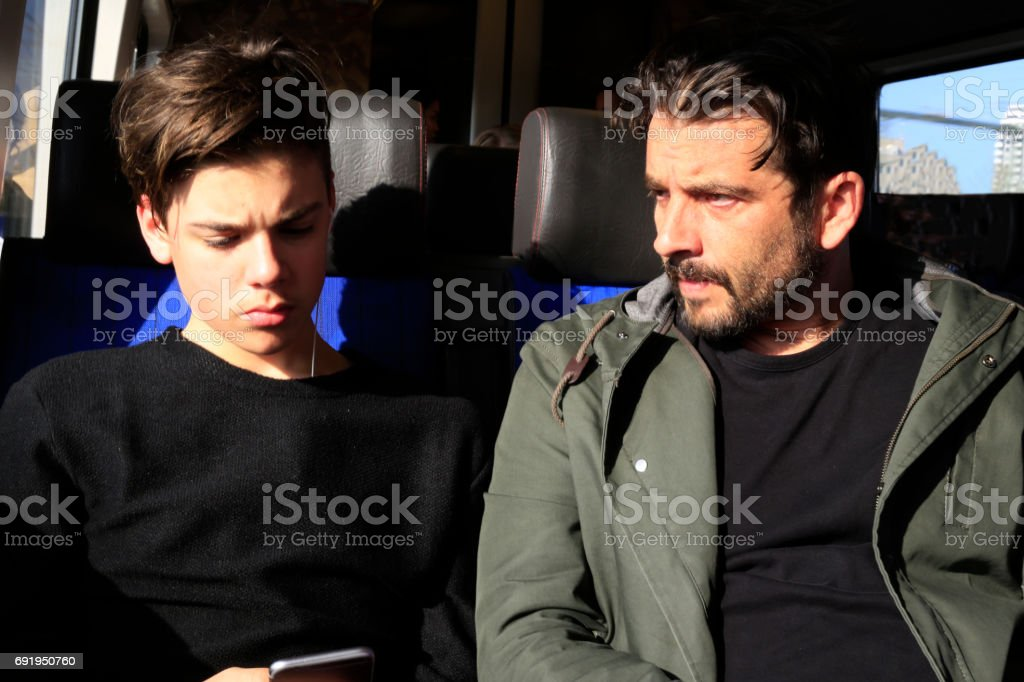 Father and teenage son traveling with train stock photo