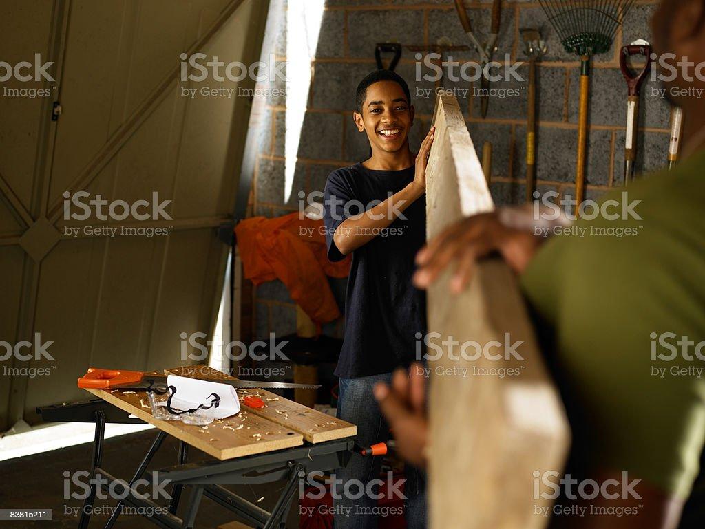 Padre e adolescente che trasportano plancia di legno foto stock royalty-free