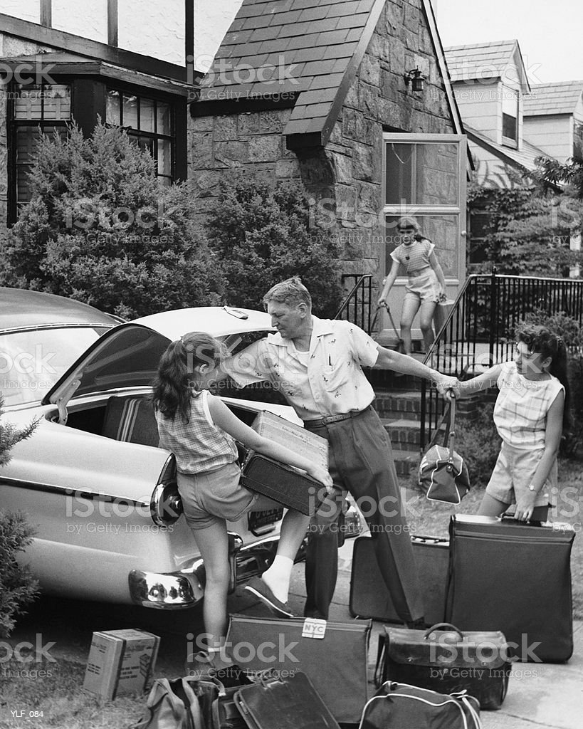 Father and three daughters loading trunk with luggage royalty-free stock photo