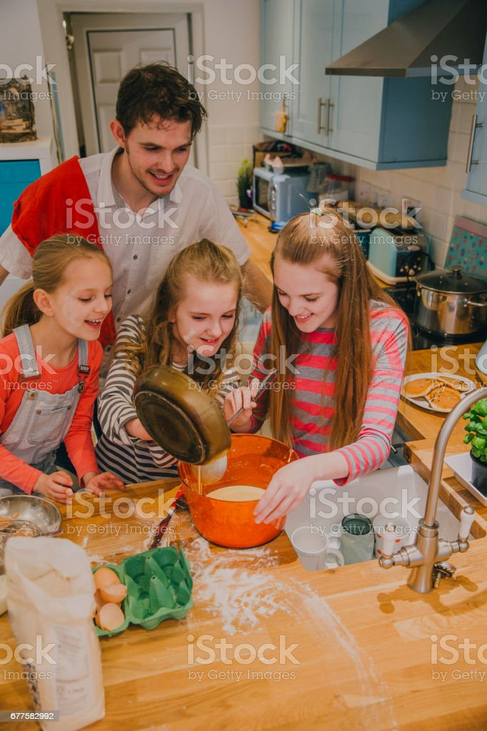 Father and Three Daughters Pouring the Ingredients into a Bowl royalty-free stock photo