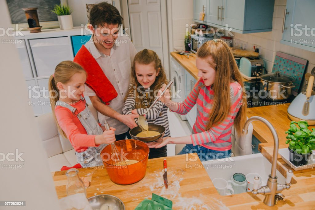 Father and Three Daughters Pouring the Mix into a Pan royalty-free stock photo