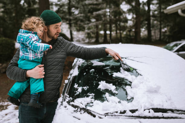 Father and Toddler Aged Girl Scrape Snow From Car