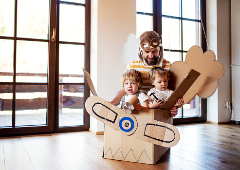 A father and toddler chidlren playing with carton plane indoors at home, flying concept.