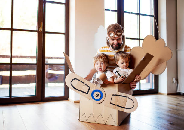 A father and toddler chidlren playing with carton plane indoors at home. A father and toddler chidlren playing with carton plane indoors at home, flying concept. father stock pictures, royalty-free photos & images
