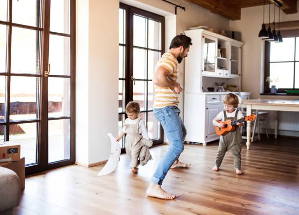 Ein Vater und Kleinkinder, die zu Hause drinnen spielen. – Foto